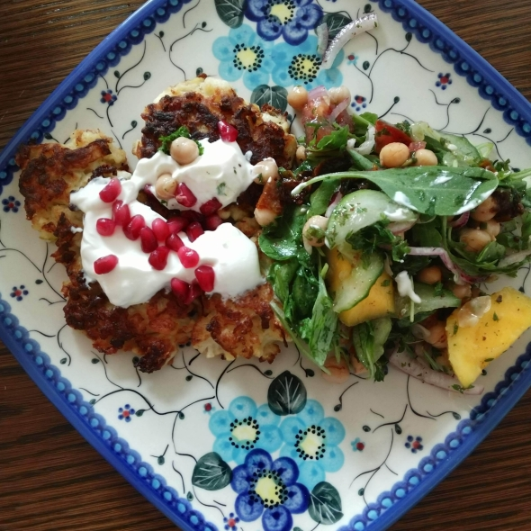 Cauliflower feta fritters with greek yogurt and pomegranate seeds with a chickpea, greens, onion, tomato, and mango salad with a honey dijon vinaigrette